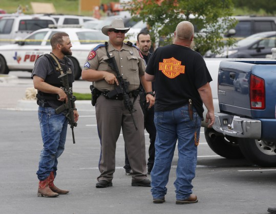 "Law enforcement officers talk to a man near the parking lot of a Twin Peaks Restaurant Sunday, May 17, 2015, in Waco, Texas, after a shooting involving rival biker gangs. Waco police Sgt. W. Patrick Swanton told KWTX-TV there were ""multiple victims"" after gunfire erupted between the gang members. (Rod Aydelotte/Waco Tribune Herald via AP)"