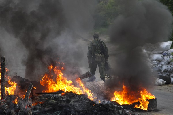 "A pro-Russian separatist guards a checkpoint while walking near burning tyres near the town of Slaviansk in eastern Ukraine May 2, 2014. Ukraine launched a ""large-scale operation"" to retake the eastern town of Slaviansk, pro-Russian separatists there said on Friday, in an escalation of violence in what has become the worst confrontation between Russia and the West since the Cold War. REUTERS/Baz Ratner (UKRAINE - Tags: POLITICS CIVIL UNREST)"