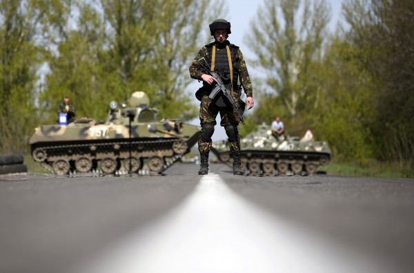 A Ukrainian soldier stand guard in front of armoured personnel carriers at a check point near the village of Malinivka, south-east of Slaviansk, in eastern Ukraine April 27, 2014. The de facto mayor of the Ukrainian city of Slaviansk said on Sunday mediators from the Organisation for Security and Cooperation in Europe who are seeking the release of a group of detained observers had arrived in the city.  REUTERS/Marko Djurica (UKRAINE - Tags: POLITICS CIVIL UNREST MILITARY TPX IMAGES OF THE DAY)