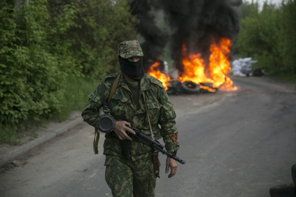 "A pro-Russian separatist guards a checkpoint as tyres burn behind him near the town of Slaviansk in eastern Ukraine May 2, 2014. Ukraine launched a ""large-scale operation"" to retake the eastern town of Slaviansk, pro-Russian separatists there said on Friday, in an escalation of violence in what has become the worst confrontation between Russia and the West since the Cold War. REUTERS/Baz Ratner (UKRAINE - Tags: POLITICS CIVIL UNREST TPX IMAGES OF THE DAY)"