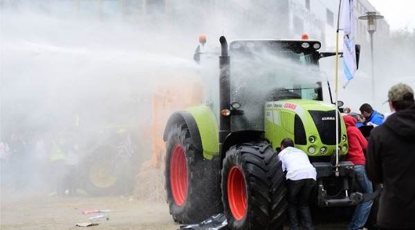 Protestors take cover behind a tractor from a water canon during a farmers demonstration in front of the European Commission building on September 7, 2015, in Brussels, as European agriculture ministers hold an extraordinary meeting at the European Council. Thousands of angry European farmers set off fireworks, blared horns and blocked Brussels streets with tractors as they demanded emergency European Union funds to help them cope with plunging food prices and soaring costs AFP PHOTO / EMMANUEL DUNAND