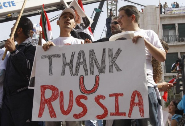 FILE - In this Oct. 12, 2011 file photo, supporters of the Syrian government hold a pro-Russian banner as they show their support for Syrian President Bashar Assad and to thank Russia and China for blocking a U.N. Security Council resolution condemning Syria for its brutal crackdown, during a demonstration in Damascus, Syria. Russian President Vladimir Putin is winning plaudits from many Syrians and Iraqis, who see Russia's military intervention in Syria as a turning point after more than a year of largely ineffectual efforts by the U.S.–led coalition battling the Islamic State group. (AP Photo/Muzaffar Salman, File)