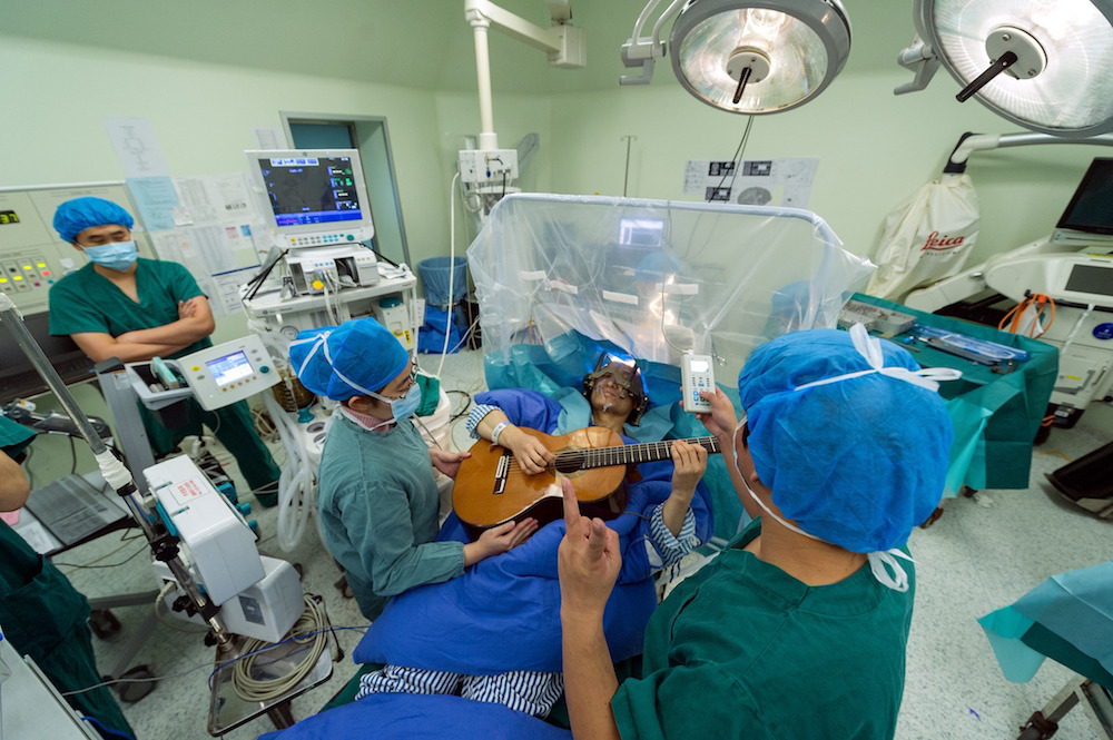 "A patient is playing the guitar while undergoing surgery on his head at Shenzhen Second People's Hospital in Shenzhen city, south China's Guangdong province, 25 January 2016. A patient played the guitar while undergoing surgery on his head at a hospital in Shenzhen city, south China's Guangdong province, on Monday (25 January 2016). The 57-year-old patient, a guitar player, is the first in China and the seventh in the world to receive ""deep brain stimulation"" (DBS), a surgical procedure in which two thin, insulated electrodes are inserted into the brain to block the signals that cause the symptoms of dystonia."