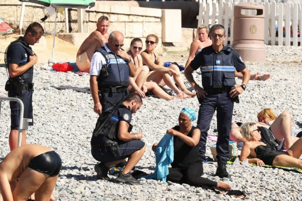 Police patrolling the promenade des anglais beach in Nice fine a woman for wearing a burkini. 23 August 2016. Please byline: Vantagenews.com