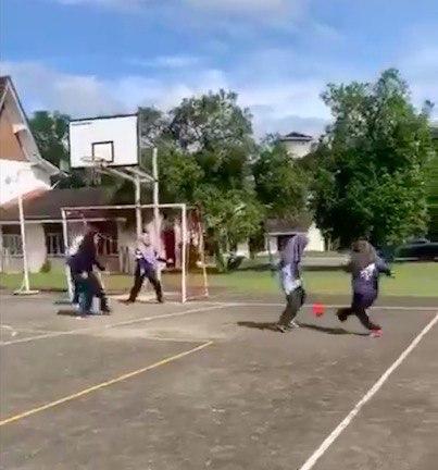 На кадрах семь девочек в спортивной форме гоняют мяч по маленькому корту, который совмещает в себе футбольное поле и баскетбольную площадку.
