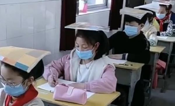 Китайским школьникам не позавидуешь. На смену странной форме пришли книги на голове, что из этого хуже