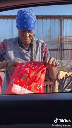 Парень отдал бездомной женщине бумажный пакет,