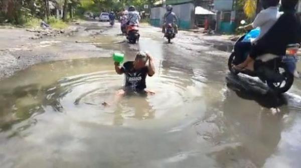 Как заставить власти сделать ремонт дороги? Для этого понадобится удочка, мыло и много дождевой воды