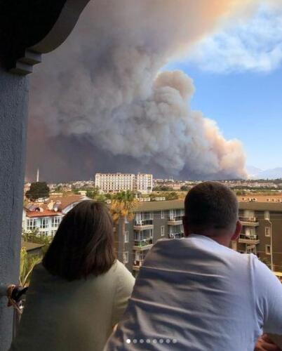Русскоязычные туристы в Турции фотографируются на фоне яркого от пожаров неба
